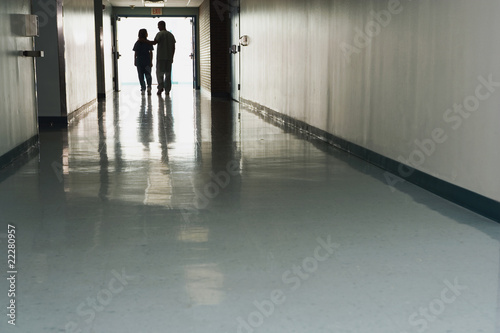 Two people standing at end of corridor in hospital