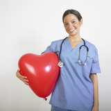 Hispanic female doctor holding heart balloon