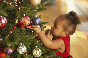 African baby girl touching Christmas tree