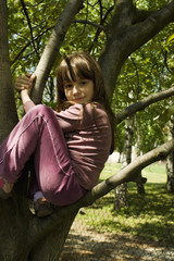 Little girl climbed on tree and sitting on tree branch