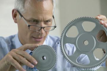 Middle-aged businessman examining gear wheels