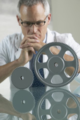 Middle-aged businessman looking at gear wheels