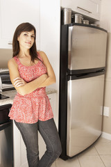 Hispanic woman with arms crossed in kitchen