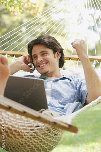 Man in hammock talking on cell phone