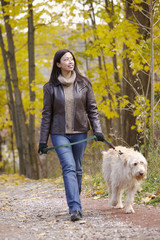 Asian woman walking dog in woods