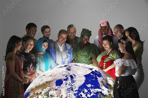 Multi-ethnic people in traditional dress looking at globe