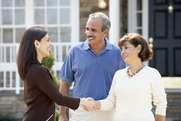 Senior Hispanic couple shaking hands with realtor