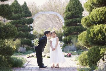 Hispanic boy and girl dressed for wedding