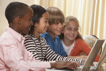 Multi-ethnic children typing on laptops