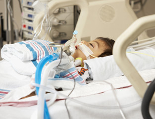 Hispanic boy in Intensive Care Unit bed