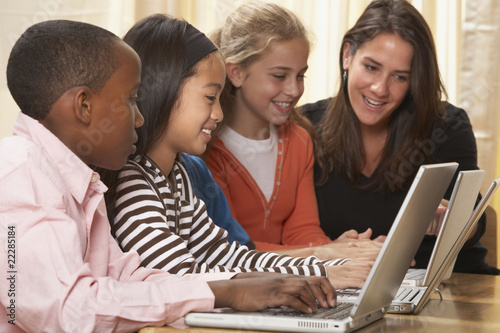 Multi-ethnic children and teacher typing looking at laptops