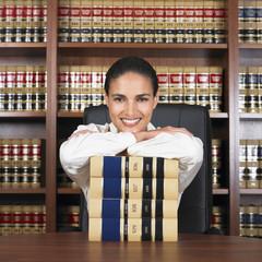 Hispanic female lawyer leaning on stack of books