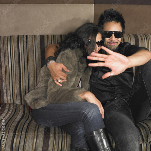 Multi-ethnic couple with hand up on sofa