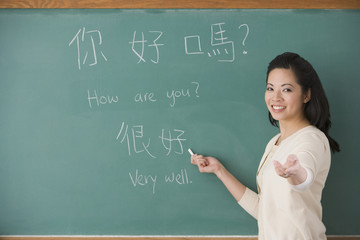 Asian female teacher writing Chinese on blackboard