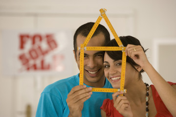 Couple holding folding ruler shaped like house