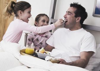 Girls giving father breakfast in bed