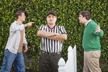 Hispanic referee between arguing neighbors