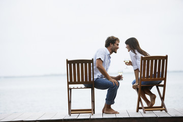 South American couple with wine on dock