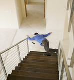 Hispanic man on floor at bottom of stairs
