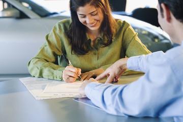 Woman signing contract at car dealership