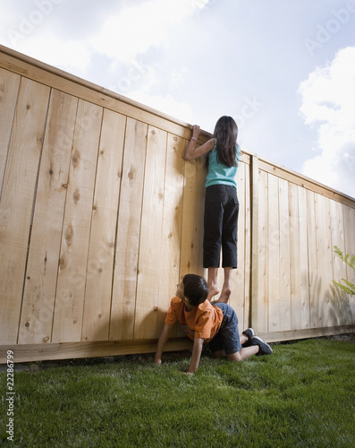 Middle Eastern girl on boy's back looking over fence