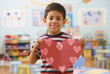 Hispanic boy holding paper cut out hearts
