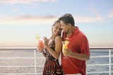 Hispanic couple with cocktails on ship