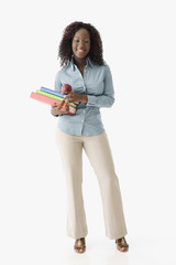 African American woman holding books and apple