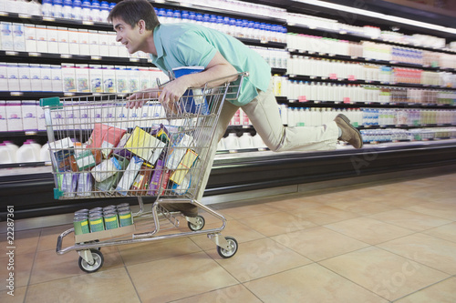 Man riding on shopping cart