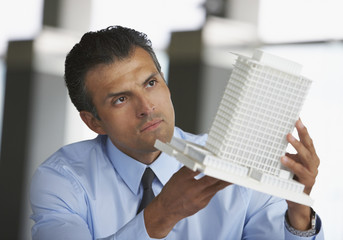 Hispanic male architect looking at model