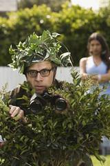 Man using bush as camouflage
