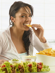 Hispanic woman eating chips