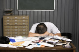 Senior Asian businessman resting head on cluttered desk