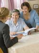 Senior Hispanic woman discussing paperwork with businesswoman