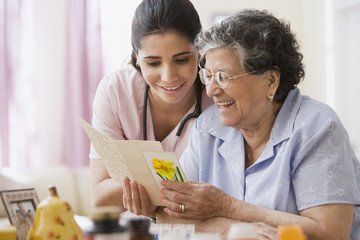 Senior Hispanic woman and nurse looking at greeting card