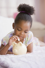 African American girl putting coin in piggybank