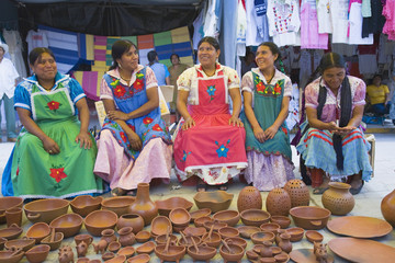 Group of indigenous Mexican women selling pottery