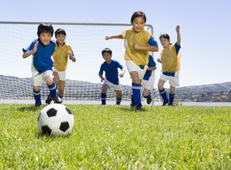 Multi-ethnic children playing soccer