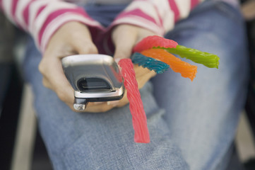 Hispanic teenaged girl holding cell phone and candy