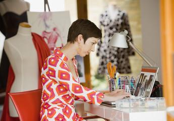 Hispanic fashion designer typing on laptop