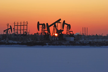 Oil rigs silhouette over orange sky-10
