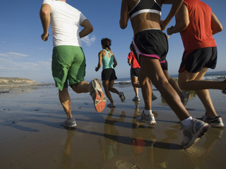 Multi-ethnic runners racing at beach