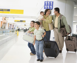 Multi-ethnic family with suitcases in airport