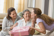 Hispanic woman giving gift to grandmother