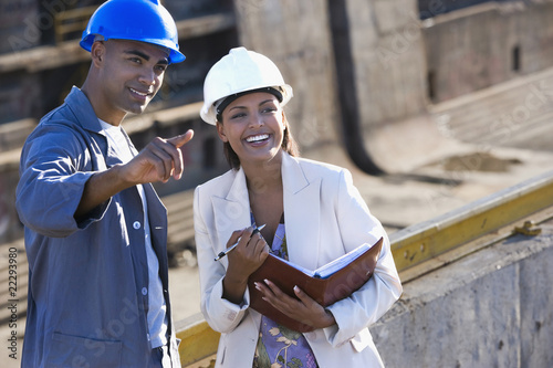 African American businesswoman and construction worker pointing