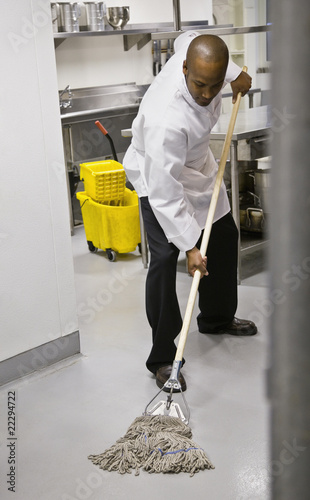 African kitchen worker mopping floor