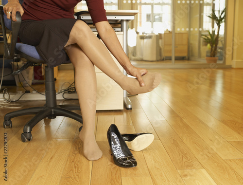 Indian businesswoman rubbing foot