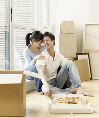Asian couple eating pizza next to moving boxes