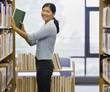 Asian woman shelving library books