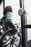 African man in wheelchair using automatic door